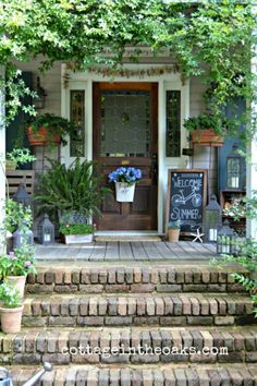 Cottage Front Porch--love this! Lanterns and sea shells and plants--all my favorite things. Love the chalk board too.