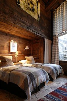 Luxury French ski chalet bedroom with rustic reclaimed unfinished wood walls, flannel plaid duvet covers, shaded wall sconces, and gray and white patterned curtains .