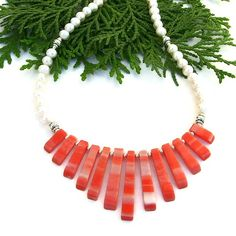 The BELLISIMO! handmade necklace might be sweet and petite, but it is big on style!  Created with a graduated orange and white stick shell fan, glowing white freshwater and sterling silver hogan beads