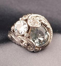 Arts & Crafts Platinum, Aquamarine and Diamond Ring, Edward Oakes, set with a fancy-cut aquamarine, and an old European-cut diamond weighing approx. 0.80 cts., further set with old mine and single-cut diamond melee, the shoulders with applied leaf motifs, size 4 1/2, unsigned.