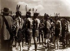 Above we show a vital photo of an Apache Feast March Ceremony. It was made in 1905 by Edward S. Curtis.    The illustration documents Several shirtless Apache men, standing with back to camera, wearing feathered headbands, and with body paintings.    We have compiled this collection of artwork mainly to serve as a vital educational resource. Contact curator@old-picture.com.