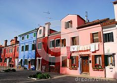 Photo made in the island of Burano in Venice in Italy. In the image they resumed colorful facades of some houses, narrow to each other, overlooking a square. Over the various colors of the houses you see the blue color of a triangle of sky.