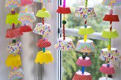 Wie bunte Schirmchen fliegen die aufgefädelten Muffinförmchen am Fenster.Eine fröhliche Deko für das Kinderzimmer, für Partys und ein Bastelspaß für die ganze Familie.