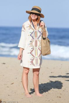 Holiday wardrobe: The mum of two looked cute in a tropical kaftan, which she used to cover...