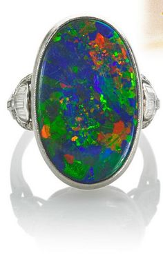 MARCUS & CO. BLACK OPAL, DIAMOND PLATINUM RING  Oval Australian black opal cabochon, 22.9 x 14 x 4.77 mm., 8.87 cts. by formula, red-orange/blue-green spectral play-of-color, in Art Deco platinum setting, diamond shoulders. Marked Marcus. Size 5 1/2. 5.0 dwt. In Marcus box. Probable gem source: Lightning Ridge. Companion to lots 2534 and 2535.