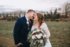 Sweet couple showing off her bridal bouquet with burgundy cymbidium orchids, seasonal greenery and white roses.