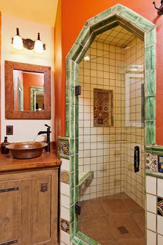 The master bath boasts a walk-in shower featuring an arched entry and insets of vividly painted ceramic Mexican tile inside. The hand-hammered vessel sink and countertop are constructed from recycled copper and reclaimed wood.