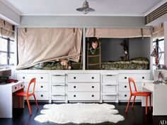 In accessories designer Fiona Kotur's Hong Kong home, the built-in beds, cabinetry, and desks in sons George (left) and Wyatt's room were made by local artisans; the ceiling light is by Pottery Barn Kids. For more genius built-in furniture ideas, check out our roundup.