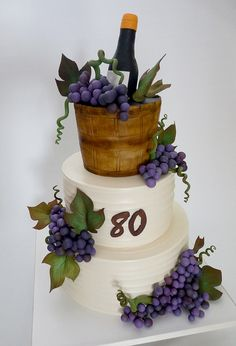 wine cake    Cake iced in buttercream, except for top tier, shaped and covered in fondant. Gumpaste grapes, leaves, vines, and wine bottle.