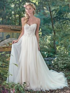 Maggie Sottero - SABINA, Sparkling Swarovski crystals, glamorous pearls, and shimmering sequins adorn the bodice of this wedding dress, before trailing into a whimsical A-line tulle skirt. Finished with sweetheart neckline and covered buttons over zipper and inner corset closure.