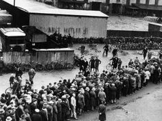 Unemployed queuing in front of the job centre in Hannover. 'Vote Hitler' is written on the wall in the background.