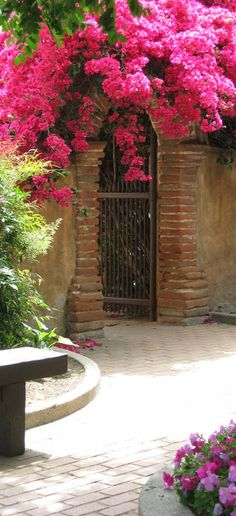Bougainvillea-covered archway at Mission San Juan Capistrano in southern Orange County, California • photo: Non Paratus on Flickr