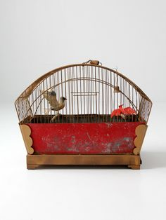 circa 1910s - 1920s This is an antique hand-painted bird cage. The arched top brass tone cage has red painted panels across the bottom half. The base of the cage slides out on the side. Within the cage two artificial birds were attached to wood perch bars, as an aged metal bell hangs from the top, and feeders are on the sides. The cage has a spring hook hang. brass tone bird cage  painted metal side panels slide out metal base spring hook hang little feeders on the inside metal bell hangs…