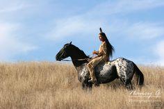 A teenage Native American boy on horseback riding the prairie of South Dakota. Nancy Greifenhagen Photography