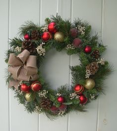 Christmas wreath artificial mixed evergreens with glistening red and gold ornaments,pine cones,pomegranates and antique pillow ticking bow