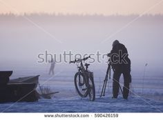 Stock Photo: Photographer on a foggy day with a bicycle and winter equipment photographing a skier in winter. -