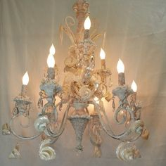 Large white chandelier with seashells and crystals heading to Miami.  www.elegantshells.com