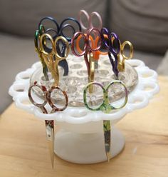 """Store your embroidery scissors in a glass flower frog. I found one of these, what I call """"candy dishes,"""" at a thrift store the other day. I popped a pin cushion in the middle and have a couple pairs of scissors sticking in the holes around the edges. I like it!"""