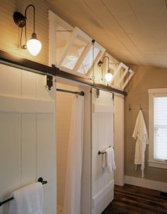 Bathroom in mountain cabin, with vintage lighting, operable transoms, sliding barn doors at the water closet and shower, heart pine floors, beadboard walls and wood ceiling | Architecture: Historical Concepts | Photo: Ri