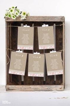 Ein Sitzplan muss nicht immer langweilig sein. Eine schöne Idee: Nutzt alte Obst- oder Weinkisten und hängt die Karten mit kleinen Clips oder Wäscheklammern auf.