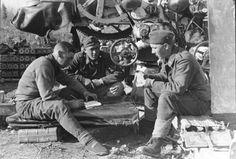 https://flic.kr/p/QRuFa9 | 1942, Union Soviétique, Des artilleurs allemands de Flak lors d'une pose. Celui de droite mélange des cartes, celui de gauche écrit dans un carnet (tient-il les comptes ?)