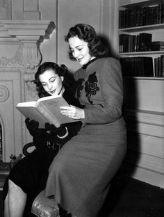 """Vivien Leigh & Olivia de Havilland reading Gone With the Wind.  """"And when Ashley came riding along, so handsome, so different, I put that suit on him and made him wear it whether it fitted him or not… I kept on loving the pretty clothes - and not him at all.""""― Margaret Mitchell, Gone With the Wind"""
