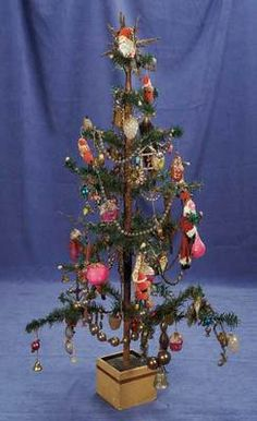 Feather-tree with wooden base, trimmed with an array of blown-glass ornaments, paper mache and crepe paper Santas, bells, clip-on birds, and garlands of glass balls. Late 19th, early 20th C.