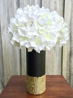 Beautiful vase, painted a flat black and dipped in gold glitter. The PERFECT addition to any party or wedding, they even make the prettiest décor for
