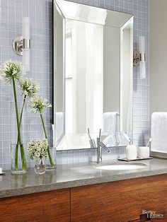 Simple bathroom design: wood vanity, wall mounted sconces, modern chrome faucet, grey stone counter, square blue wall tile, simple mirror with mirrored framed