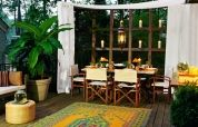 Set the stage for dinner with a sunshade valance and fabric panels that frame a candle wall grid like a window.  Similar to shown: Coolaroo Square Shade Sail, about $130; Walmart. Outdoor curtains, about $70 per panel; Plow & Hearth