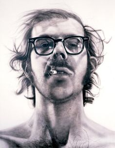 """Big Self-Portrait"" by Chuck Close between 1967-68. Although it seems to be a photograph it's actually acrylic on canvas. This painting is almost 9 feet by 11 feet in size and took four months to complete. He started with a photograph and drew a grid on the photo where he then carefully transferred the image square by square onto the large canvas. In his photo the back of his hair and the tip of his cigarette were out of focus so he painted them that way in his portrait."