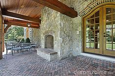 luxury masonary fireplaces   Brick patio outside luxury home with stone fireplace