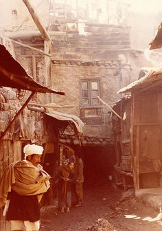 Title: Kabul Side Streets Description: An Afghan Man and Young Children gather near Shops in the Old Quarters of the Capital. Location: Kabul, Eastern Afghanistan. Circa: 1978 Photographer: Noor Khan