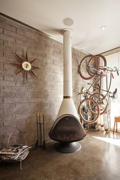 Malm fireplace in a mid-century living room with concrete floors and bike storage.
