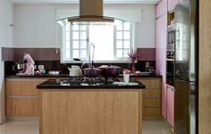 A arquiteta Letícia Arcangeli criou o armário rosa da cozinha. Os da bancada e da ilha central ela revestiu de laminado amadeirado para o ambiente não ficar tão feminino, mas para o uso de toda a família