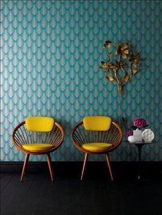 turquoise wallpaper, yellow vintage chairs, brass wall ornament