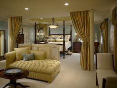 This elegant master bedroom features columns with tie-back draperies to separate the sleeping area from the sitting room. A custom floor screen diffuses the hydraulic TV cabinet facing the four poster bed. The curtain on the left side of the bed surrounds a mirror instead of a window to open up the space.