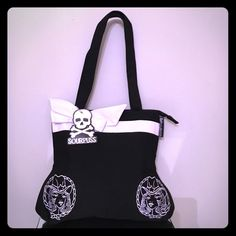 "SOURPUSS ROCKABILLY COWGIRL BLACK TOTE in package You are viewing hey super cool rockabilly name brand called sourpuss! Their items completely rock! This is a beautiful totebag measuring 14"" x 14"" in a pear shape with the bottom being a little larger (top approx 12"") , cute white goose grain bow and detail! Mikell girls are embroidered on the bag, double strap drop approximately 10 inches bag is canvas with easy care, sourpuss tag inside and out! Hang tag also, nylon checkered lining with…"