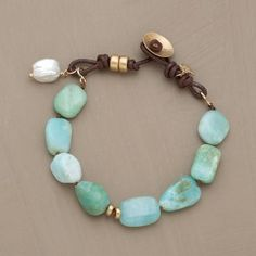 Peruvian opals, satin-finished gold, a cultured nugget pearl. Leather loop and gold button clasp.