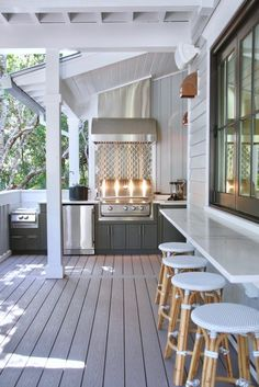 Southern Living Idea House 2017: Tucked in the back corner is a super shiny & uber efficient outdoor kitchen decked out with all the bells and whistles. In the center is the stainless steel grill and hood that brings your eye up. Charcoal painted cabinetry house a beverage cooler, additional stove, pot filler, hide-a-way blender and a convenient bar sink. What more could any porch party need? #deltaliving
