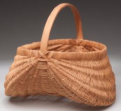 "APPALACHIAN RIB-TYPE WOVEN VINE BASKET, probably honeysuckle, finely woven exaggerated kidney form with white oak ribs, rim and arched handle. Original natural surface.  Mid 20th century. 10 1/2"" HOA, 6"" H rim, 9 1/2"" x 10 1/2"" rim."