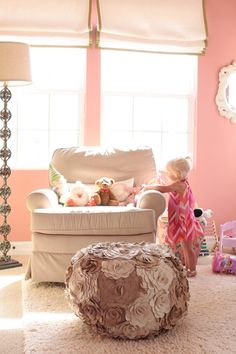 adorable -- meohmymama.blogspot.com  Ashlee Raubach Photography    Adorable pink girl's nursery design with pink walls paint color, white roman shades with green ribbon trim, stacked glass balls floor lamp, soft pink slip-covered glider, ivory wool rug and Arteriors Alana Ottoman flower Pouf.