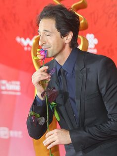The Grand Budapest Hotel's Adrien Brody stops to smell the multi-colored roses during Wednesday's closing ceremony at the Beijing International Film Festival China's BTV Grand Theater. Adrien Brody, Grand Budapest Hotel, Broody, Tribeca Film Festival, Star Track, Michelle Williams, April 25, Close Your Eyes, International Film Festival