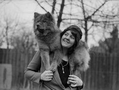 1930: Mrs. Bernard Cathbert drapes one of her chow dogs around her shoulders in the garden of Omar House, Catford, London.