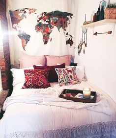 Cute maroon pillows on a white bed with interesting wall hanging