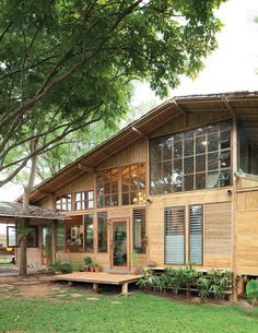 A bamboo house with modern appeal sits encompassed by its natural surroundings. It's also a medical clinic that says a lot about the doctor/homeowner's interest in the natural therapeutic concept. Discover the joy of a peaceful country setting. Modern Tropical House, Tropical Houses, Bamboo House Design, Bamboo Building, Hut House, Bamboo Architecture, House Architecture, Wooden House, House In The Woods