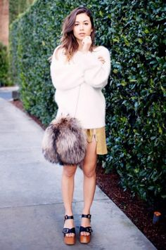 Street Style Trend: Fur Accessories - Rumi Neely wearing an oversized fur crossbody bag with platform sandals, + fuzzy sweater and mini skirt