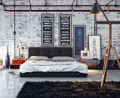 quarto com decoração estilo industrial, parede de tijolos a vista rústica branca, cama preta com roupa de cama cinza, quadros retangulares compridos na parede, pé direito duplo, tubulação aparente, malas como criado mudo