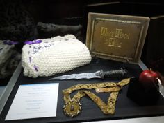 I REALLY want the dagger! A collection of props from Once Upon A Time, including Emma's baby blanket, Henry's Book, Rumplestiltskin's dagger, Regina's poisoned apple, and the giant's bean pendant necklace.
