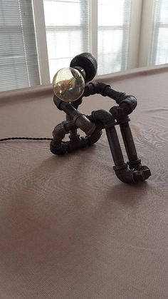 Handmade lighted sculpture that is made from black industrial plumbing pipe. This lighted sculpture measures approximately 10 inches tall and has a footprint of 7 x 10 inches. Works with standard three prong 110V outlet. Comes fully assembled. #pipelamp